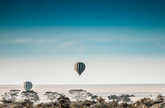 Two air balloons in the sky over the Serengeti in early morning.