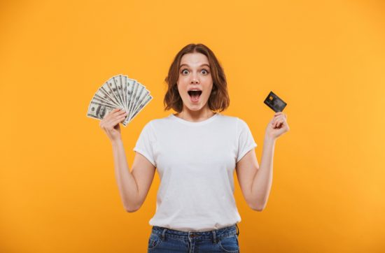 happy young woman holding money and a credit card