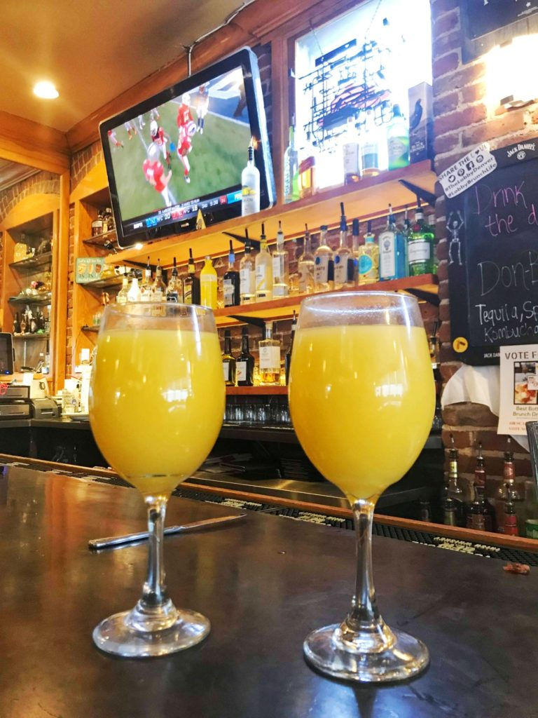 Bottomless mimosas Denver - Two wine glasses filled with mimosas sit on a bar. Bottles and a tv in the background.