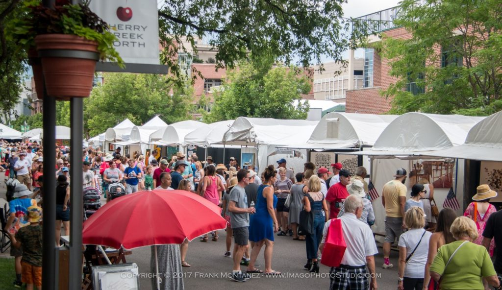 A crowd of people exploring vendor booths at the Cherry Creek Arts Festival in Denver