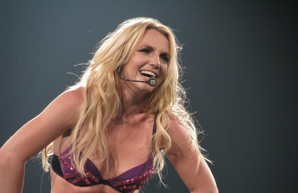 Britney Spears laughing into her microphone while performing