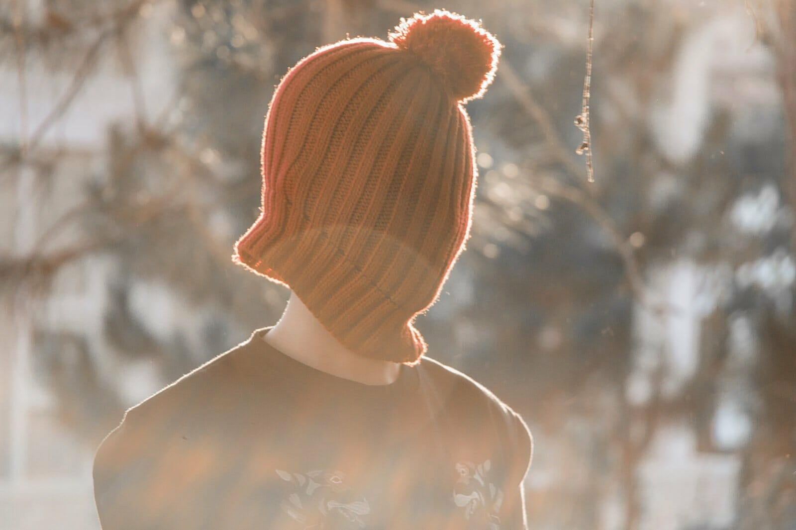 Funny travel stories - A person is wearing an orange stocking cap over their face and head