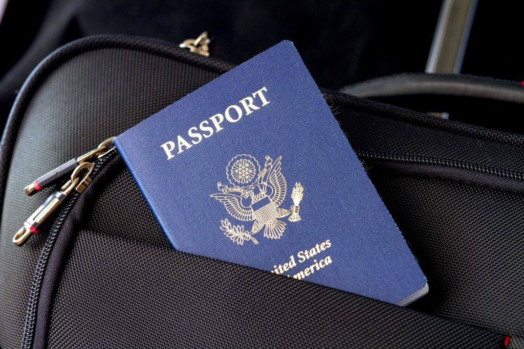 A blue US passport sticks out of the pocket of black luggage