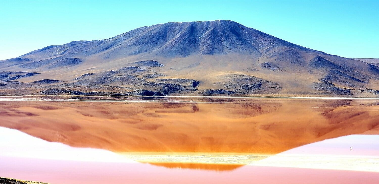 A red lake with a mirror-like reflection of the mountain behind it