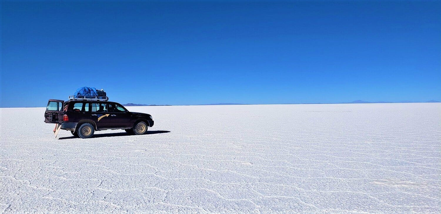 Uyuni salt flats tour Jeep sits on a sprawling salt flat with hexagon shapes dried into it