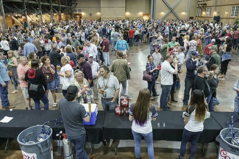 A large gathering of people in an indoor open space sampling craft beers