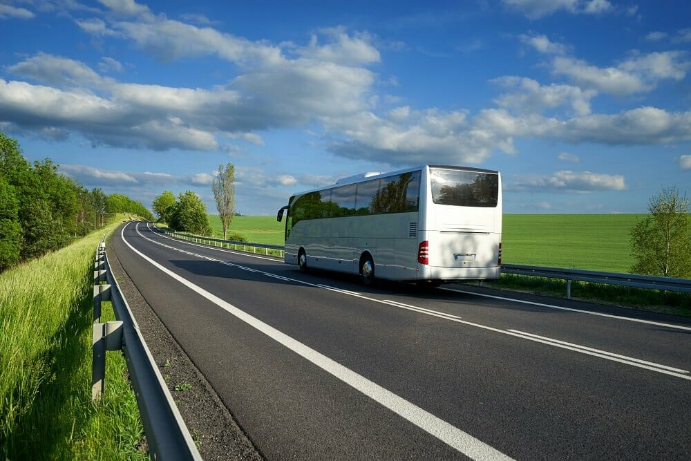 A large white bus drives down an empty two lane highway splitting a large green space