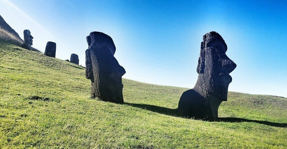 Two large moai heads stand upright in the grass with blue skies behind them