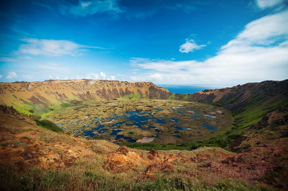 A volcanic crater (called Rano Kau) on Easter Island with the ocean in the background