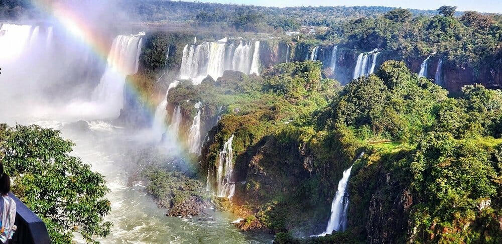 Many large waterfalls nestled in the jungle with a rainbow in the foreground