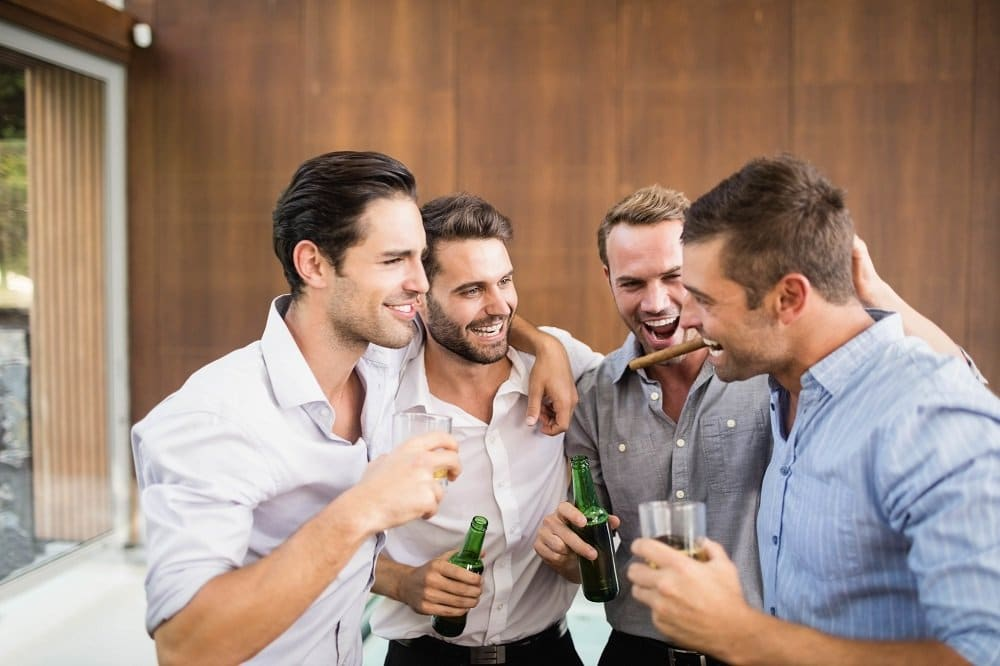 Group of four young men having drinks at a bachelor party in denver
