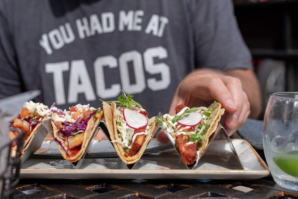 Closeup of a man reaching for a taco platter with four tacos