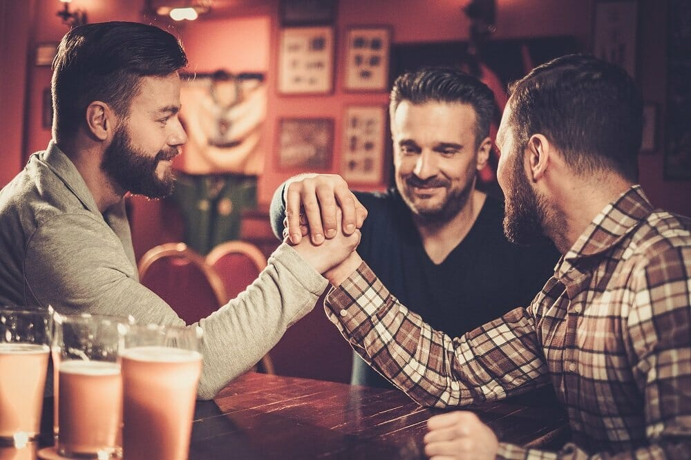 Three male friends have fun arm wrestling each other in a pub