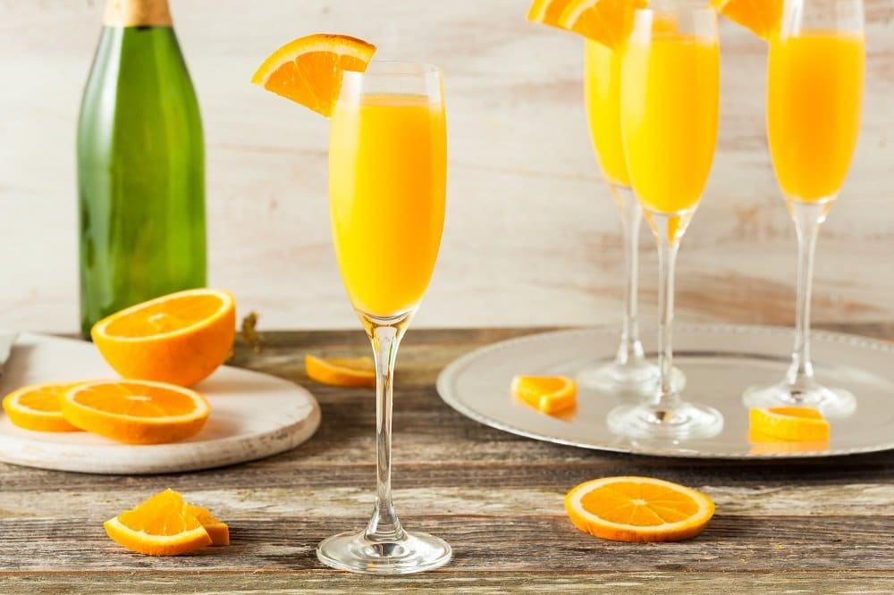 A table is adorned with orange mimosas in champagne flutes, a champagne bottle and sliced oranges