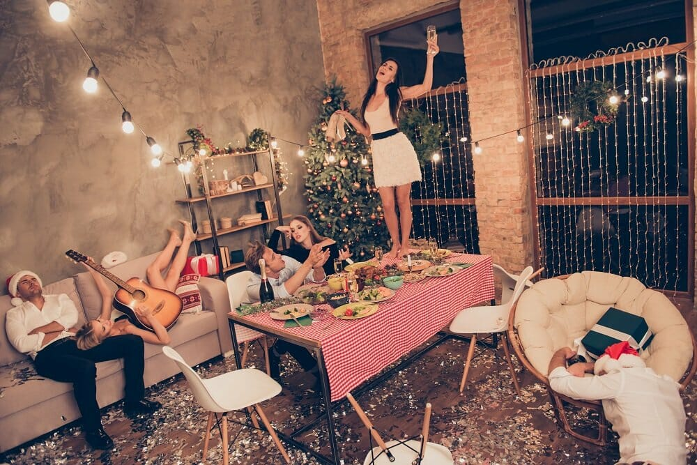 A girl in white stands on table with martini, guys sleeping, house a mess