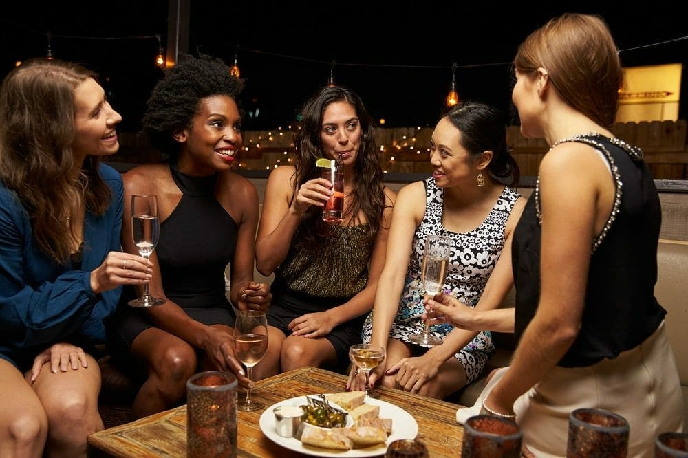 A group of female friend enjoy a night out with food and drinks at a rooftop bar