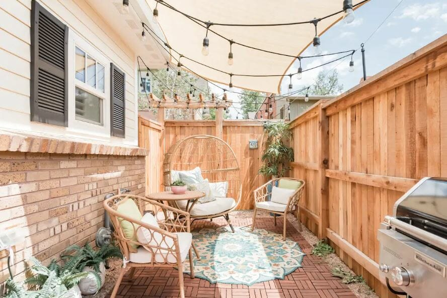 private patio with seating and overhead string lighting