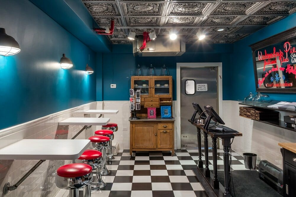 A room with an old-school diner feel including black and white checkered floors, red barstools and white table tops