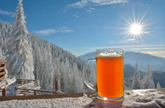A glass beer stein full of beer sits on a table with a winter wonderland in the background