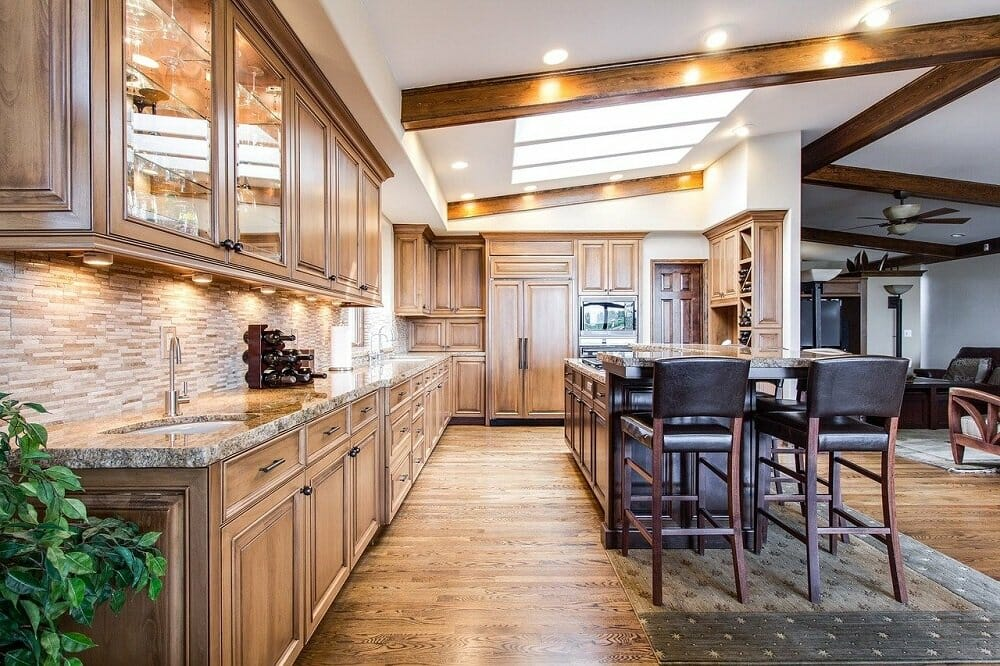 Airbnbs in Denver often come with warm, modern kitchens like pictured with wood cabinetry and a large island with seating
