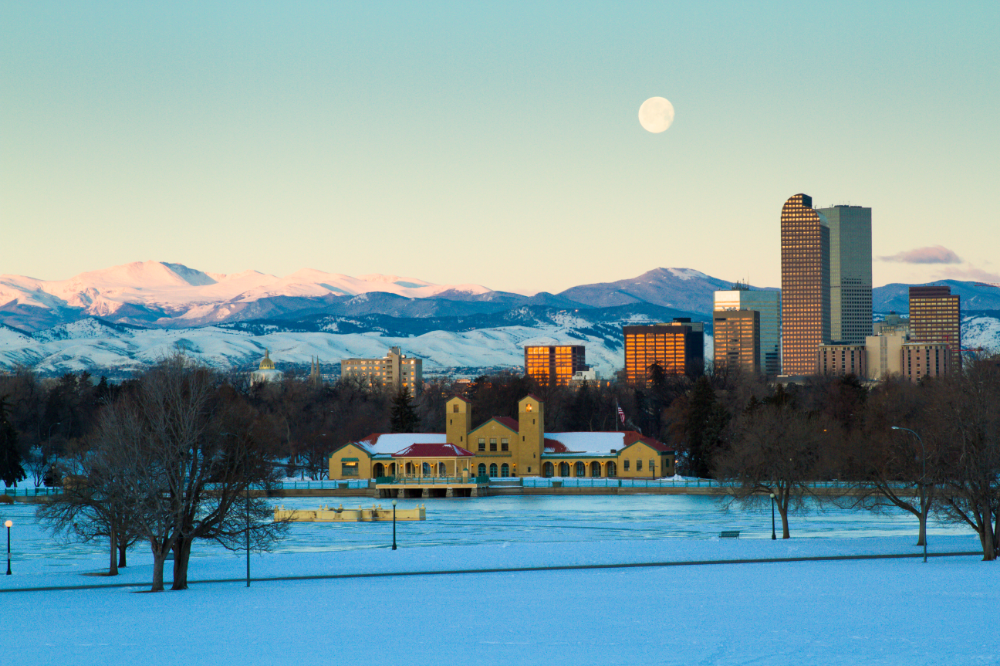 City park, the downtown Denver skyline, and rocky mountains all draped in white snow