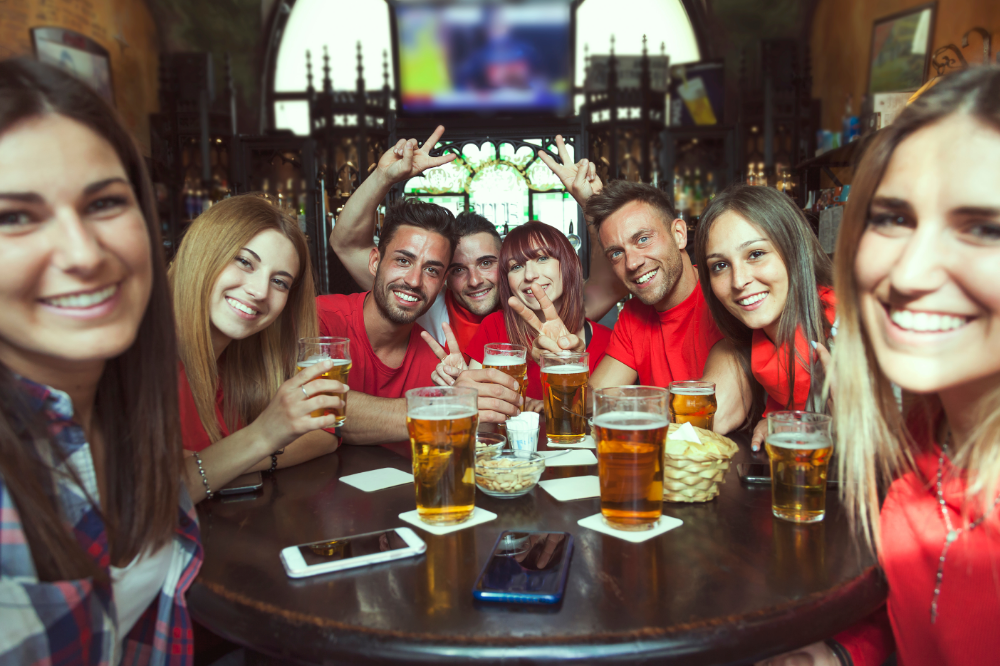A group of 8 friends pose for a picture at a bar table, most wearing red; pints of beer and cell phones on the table