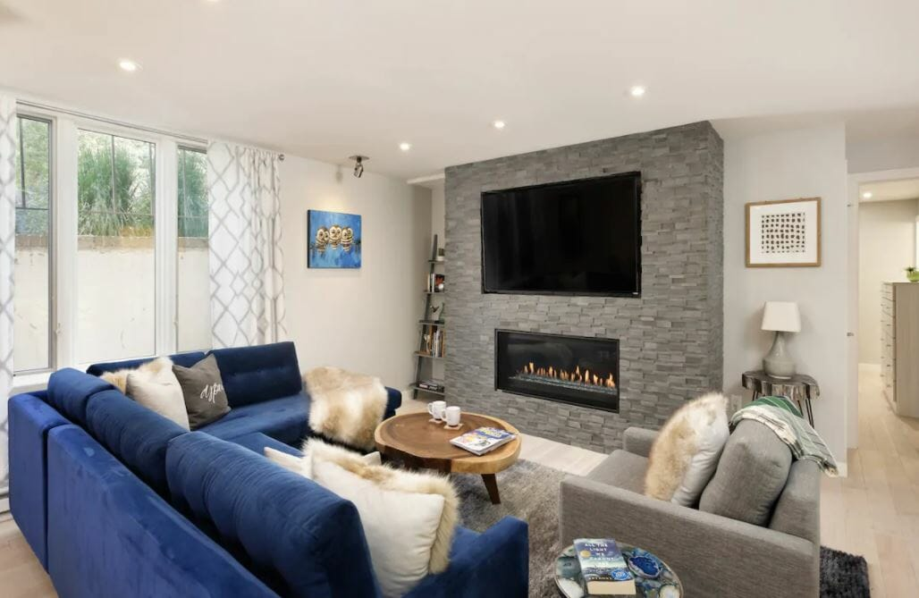 modern living room with large gray fireplace and bright blue sectional couch