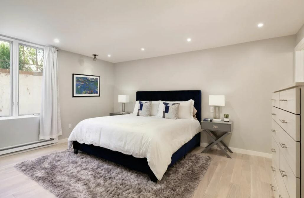 large bedroom with light gray walls, gray shag rug and white bedding