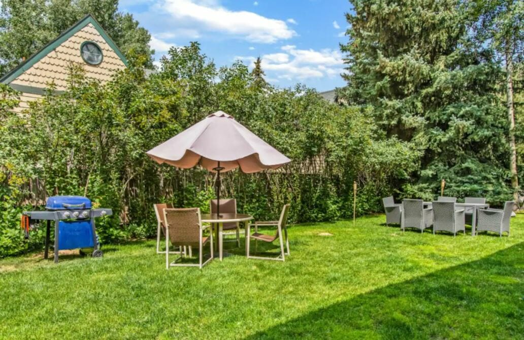 bright green backyard with bbq grill and table with beige umbrella