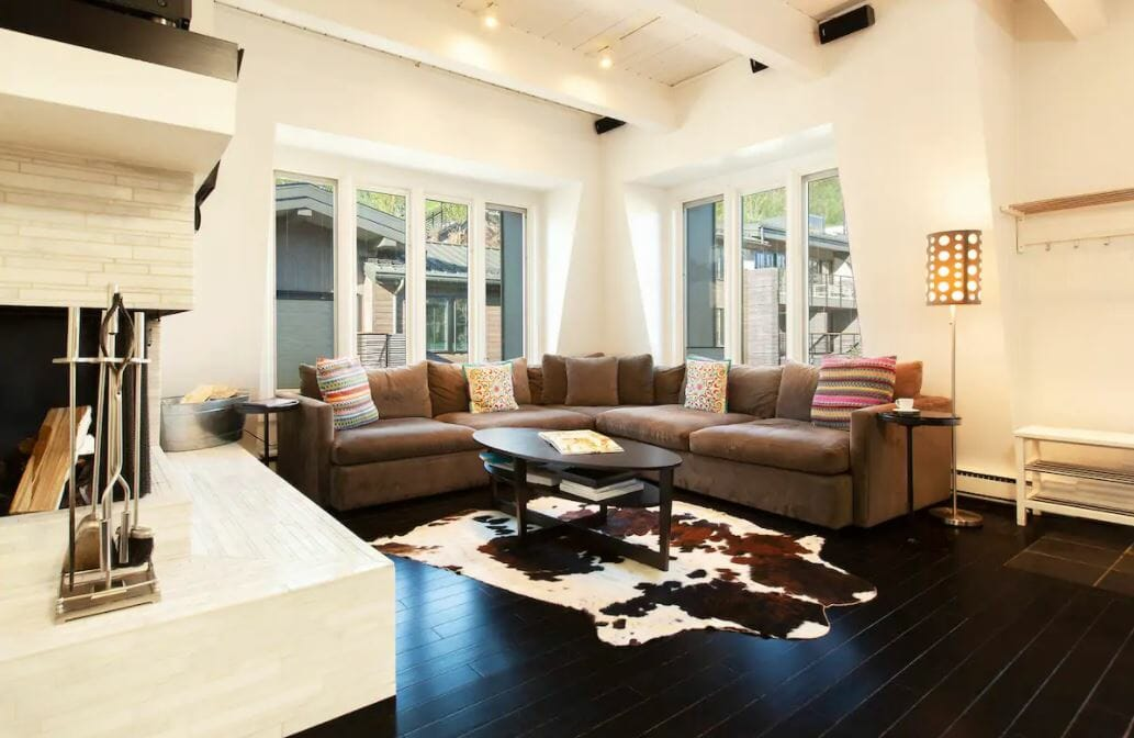 bright white living room with large sectional cough and animal skin rug
