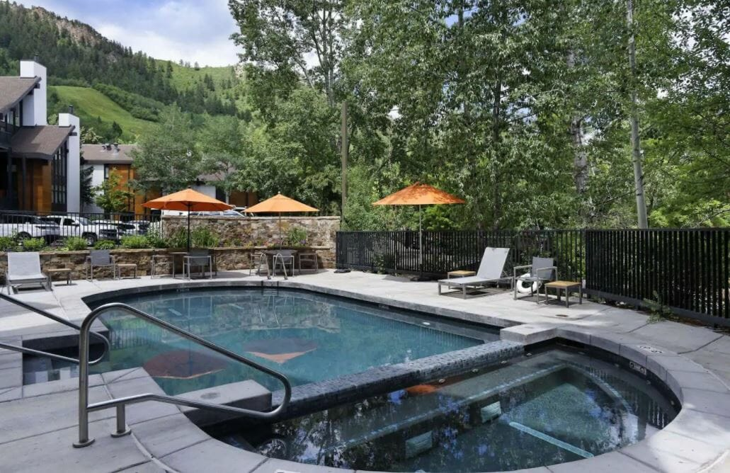 An outdoor dual pool and hot tub, tables with orange umbrellas, green trees and grass beyond