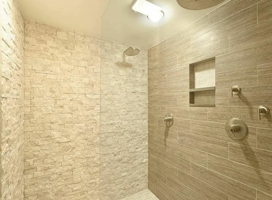 A beige, stone walk-in shower with glass partition and rain shower head