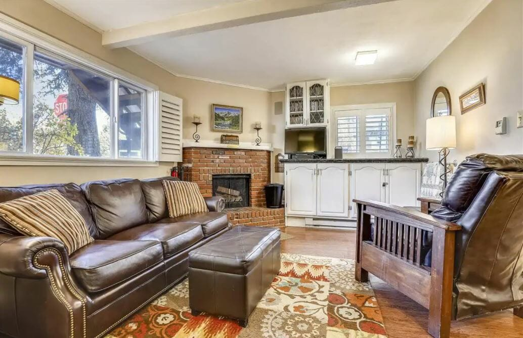 Comfortable living room with brick fireplace, leather furnishings and beige walls