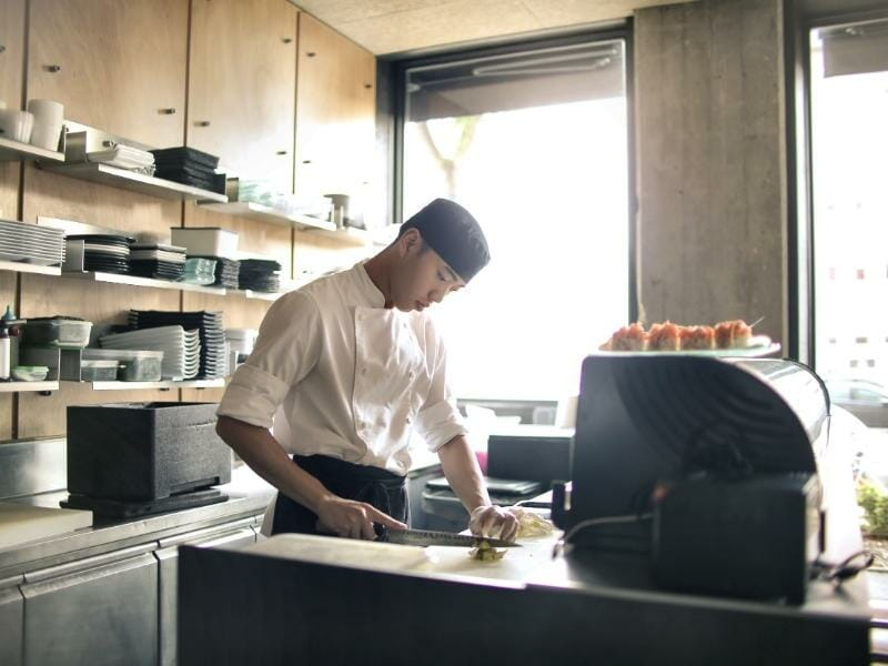 A sushi chef concentrates on slicing; dishes stacked on shelves behind him