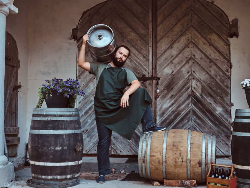 A male brewer in an apron poses with kegs, barrels and bottles