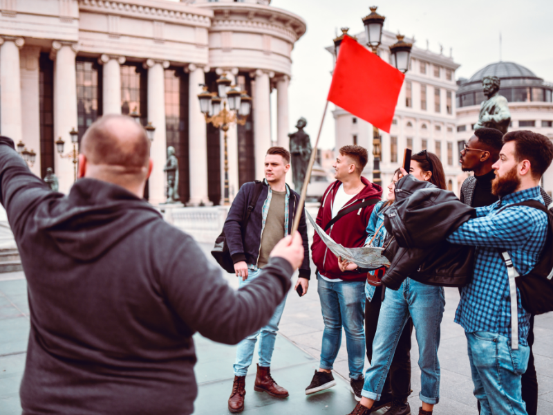 A tour guide holds a red flag while pointing, tour group of six people look on
