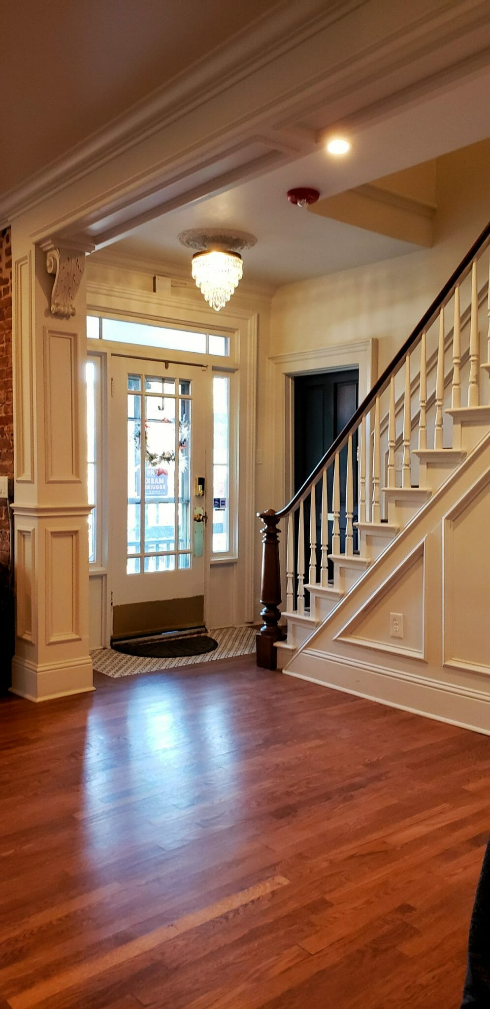 Historic details in the hotel entryway - original hardwood floors, a mini chandelier and intricate woodwork on the stairs