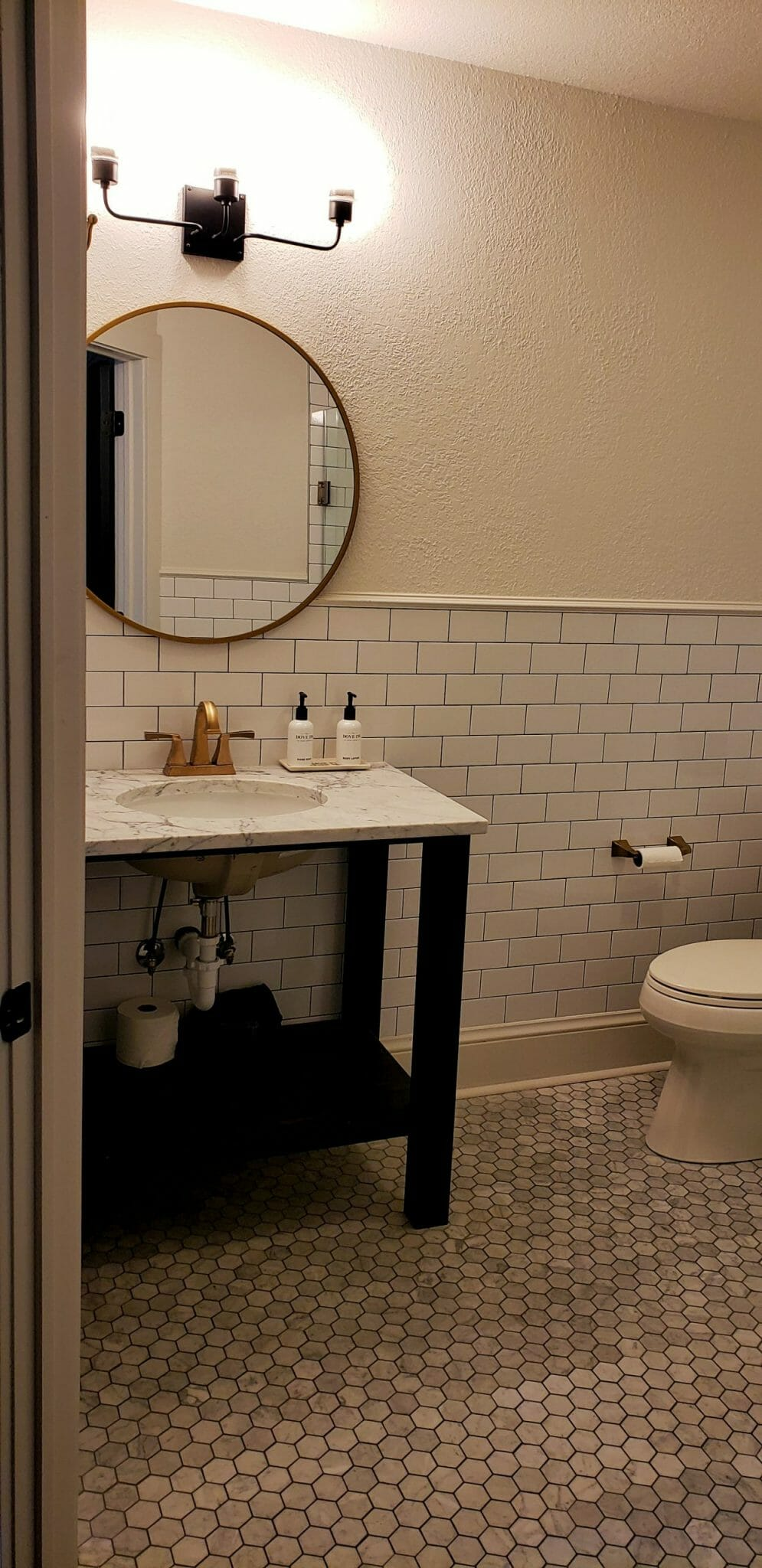 Bathroom with round mirror, marble countertop and white subway tiles