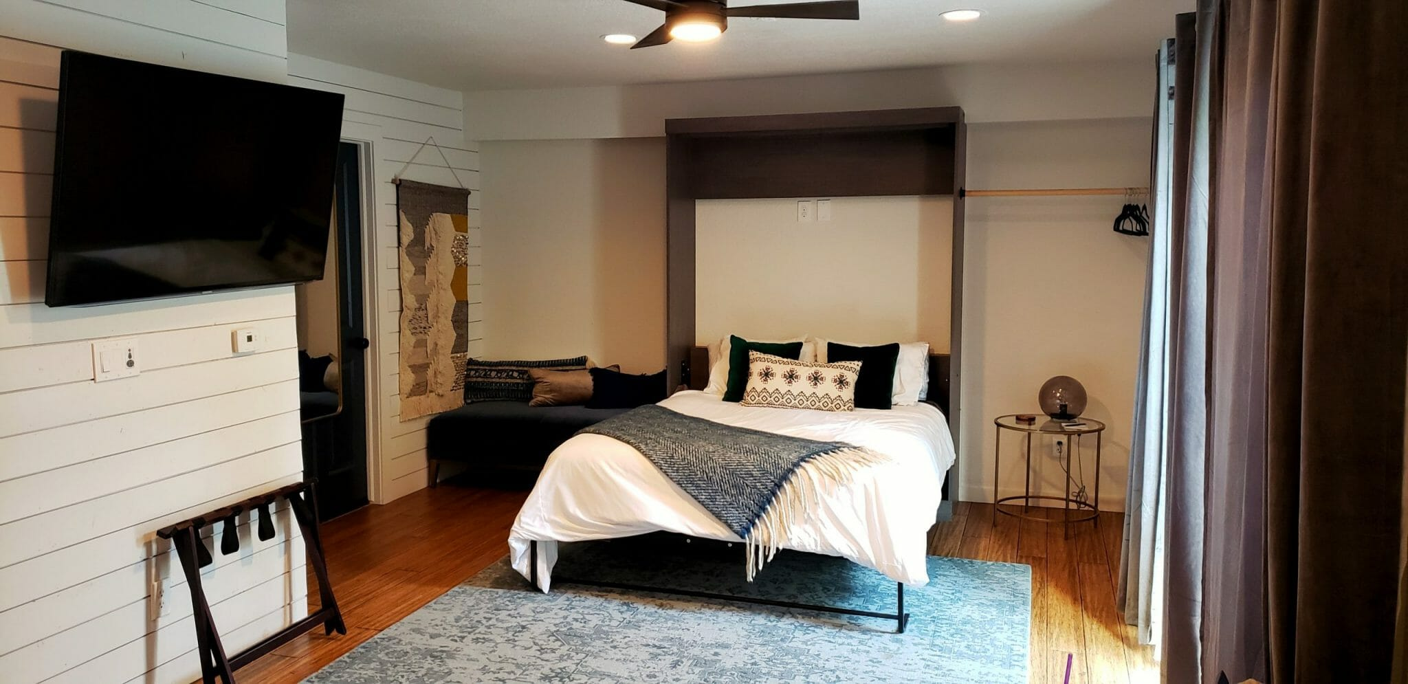 Hotel room sleeping area with white bedding and large blue area rug