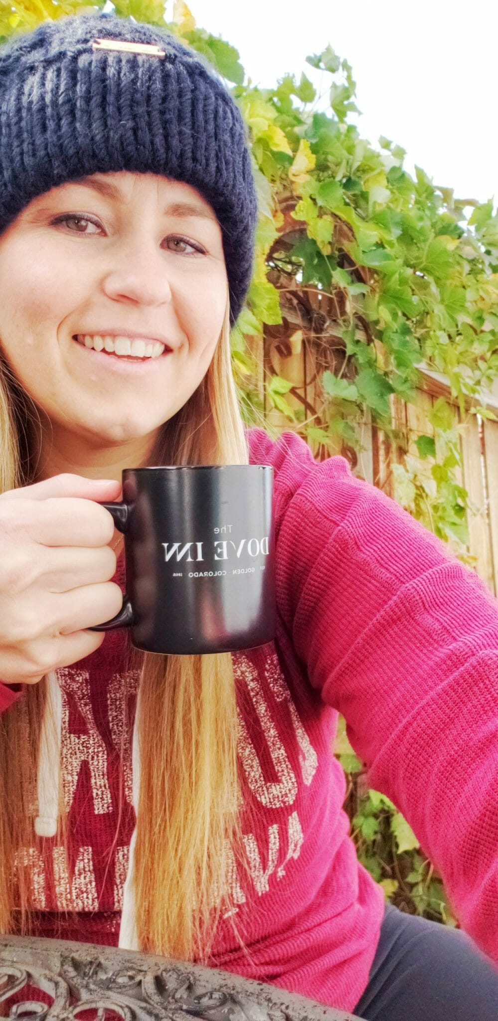 A woman with long blond hair wearing a black beanie holds a black coffee cup that says