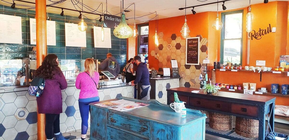 Three people are being served at a cafe service line; orange accent wall