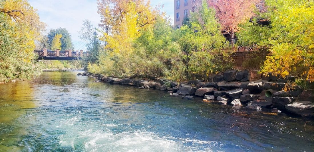 A river with a rocky bank and fall colored trees lining it; bridge crossing the river in the background
