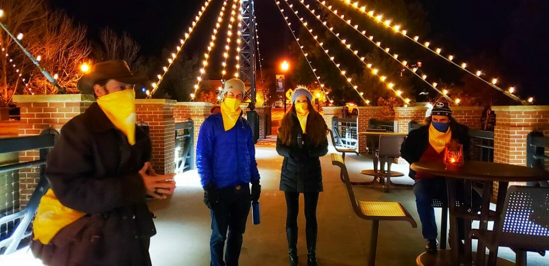 A group of people with yellow bandanas on their face listean to a tour guide; standing on bridge with overhead bulb lights