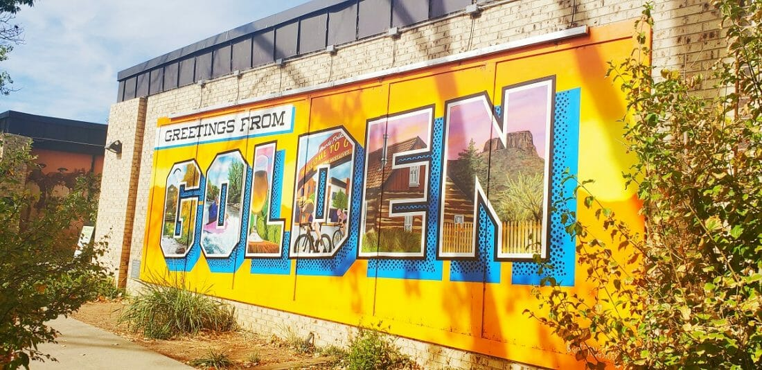 """An orange painted sign on a brick wall reads """"GREETINGS FROM GOLDEN"""""""