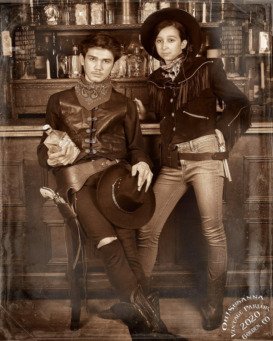 A young man and woman pose for a black and white wild west photograph; scene set to look like an old saloon