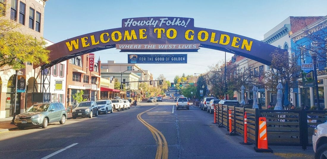 """things to do in golden colorado: a """"welcome to golden"""" arched sign over main street lined with shops and cars"""