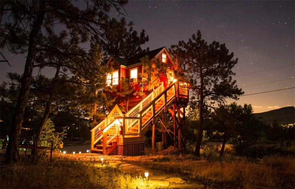 A treehouse rental lit up amongst the trees and a nighttime sky