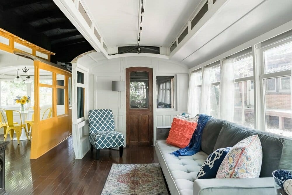 Living room of a converted trolley car including a couch and accent chair, white walls with one yellow accent wall