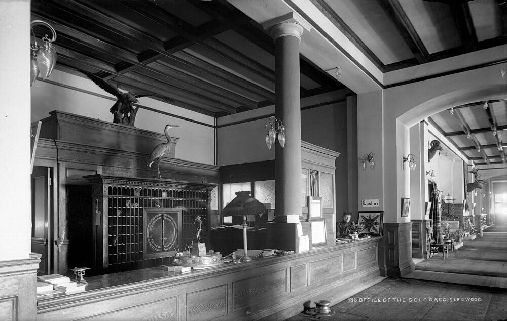 Black and white photograph of an old hotel lobby; woman working behind the counter