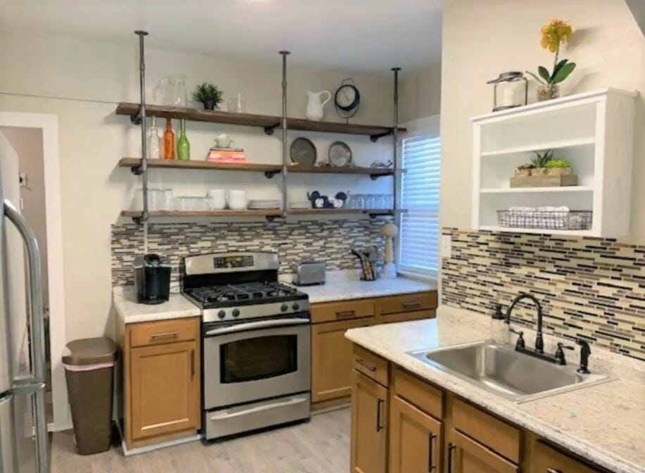 A cozy kitchen with open shelving and stainless steel appliances